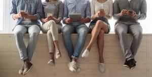 אנשים יושבים על חומה עם נייד